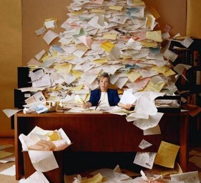 vrouw achter bureau met berg papier